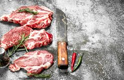 Raw meat of beef with rosemary and hot peppers. On rustic background Stock Photo
