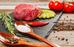 Raw meat, beef with spices for cooking on black board. Raw beef steak and spices for cooking. Fresh meat on slate black board stock image