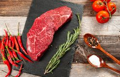 Raw meat, beef with spices for cooking on black board. Raw beef steak and spices for cooking. Fresh meat on slate black board stock images