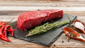 Raw meat, beef with spices for cooking on black board. Raw beef steak and spices for cooking. Fresh meat on slate black board royalty free stock photo