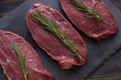 Raw meat, beef steak with rosemary on black background. Three items. Close up. Raw meat, beef steak on black background, top view Royalty Free Stock Photo