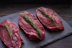 Raw meat, beef steak with rosemary on black background. Three items. Close up. Raw meat, beef steak on black background, top view Stock Photos