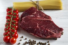 Raw meat, beef steak, brench of ripe cherry tomatoes, spaghetti,. Raw meat, beef steak, brench of ripe cherry tomatoes, spaghetti Royalty Free Stock Photography