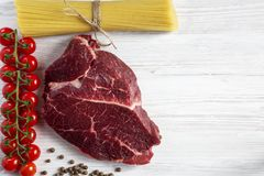 Raw meat, beef steak, brench of ripe cherry tomatoes, spaghetti,. Pepper. Top view. Flat lay Royalty Free Stock Photo