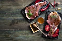 Raw meat, beef steak. Raw meat with herbs, honey and spices on old wooden background. Raw pork steak. Ingredients for cooking meat flat lay copy space Royalty Free Stock Photos
