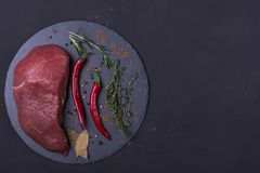 Raw meat beef steak. With spice on dark background Royalty Free Stock Photos