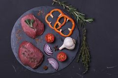 Raw meat beef steak. With spice on dark background Stock Photo