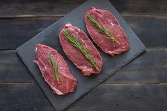Raw meat, beef steak with rosemary on black background. Three items. Raw meat, beef steak on black background, top view Royalty Free Stock Image