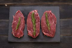 Raw meat, beef steak with rosemary on black background. Three items. Raw meat, beef steak on black background, top view Royalty Free Stock Photo