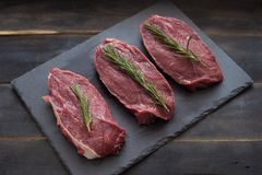 Raw meat, beef steak with rosemary on black background. Three items. Raw meat, beef steak on black background, top view Stock Photo