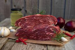 Raw meat, beef steak on rustic wooden table with spices stock images