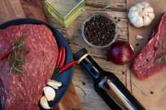Raw meat, beef steak on rustic wooden table with spices stock photo