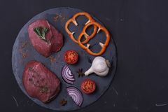 Raw meat beef steak. With spice on dark background Stock Photos