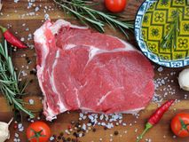 Raw meat, beef steak with spice, tomato and olive oil stock images