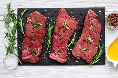 Raw meat, beef steak with spices, olive oil and rosemary on black slate cutting board over wooden background. Top view Stock Photo