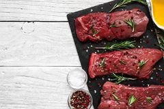 Raw meat, beef steak with spices, olive oil and rosemary on black slate cutting board over wooden background. Top view with copy space Royalty Free Stock Photography