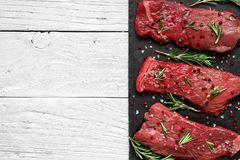 Raw meat, beef steak with spices and rosemary on black slate cutting board over wooden background. top view with. Copy space Royalty Free Stock Photo