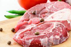 Raw meat beef steak and vegetable on wooden cutting board. Close-up. Raw meat beef steak and vegetable on wooden cutting board. Close up Stock Images