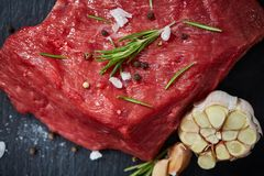 Raw meat beef steaks on black slate board with spices, garlic and rosemary over wooden background, selective focus. Raw meat beef steaks on black slate board Royalty Free Stock Photo