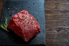 Raw meat beef steaks on black slate board with spices and rosemary over wooden background, copy space. Preparation for cooking. Hight quality barbeque. Gourmet Royalty Free Stock Photos