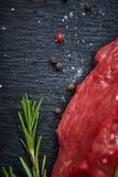Raw meat beef steaks on black slate board with spices and rosemary over wooden background, copy space. Preparation for cooking. Hight quality barbeque. Gourmet Stock Photos
