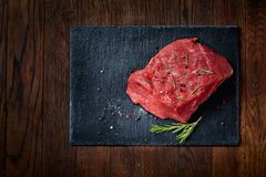 Raw meat beef steaks on black slate board with spices and rosemary over wooden background, copy space. Preparation for cooking. Hight quality barbeque. Gourmet Stock Image