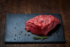 Raw meat beef steaks on black slate board with spices and rosemary over wooden background, copy space. Preparation for cooking. Hight quality barbeque. Gourmet Stock Photo