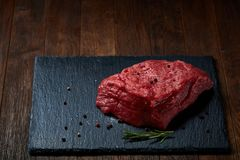 Raw meat beef steaks on black slate board with spices and rosemary over wooden background, copy space. Preparation for cooking. Hight quality barbeque. Gourmet Royalty Free Stock Images