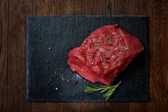 Raw meat beef steaks on black slate board with spices and rosemary over wooden background, copy space. Preparation for cooking. Hight quality barbeque. Gourmet Royalty Free Stock Photo