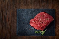 Raw meat beef steaks on black slate board with spices and rosemary over wooden background, copy space. Preparation for cooking. Hight quality barbeque. Gourmet Stock Photography