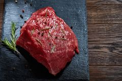 Raw meat beef steaks on black slate board with spices and rosemary over wooden background, copy space. Preparation for cooking. Hight quality barbeque. Gourmet Royalty Free Stock Image