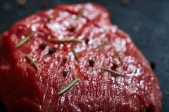 Raw meat beef steaks on black slate board with spices and rosemary over wooden background, copy space. Preparation for cooking. Hight quality barbeque. Gourmet Stock Images