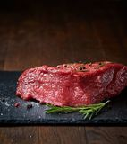 Raw meat beef steaks on black slate board with spices and rosemary over wooden background, copy space. Preparation for cooking. Hight quality barbeque. Gourmet Royalty Free Stock Photography