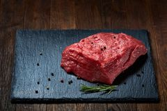 Raw meat beef steaks on black slate board with spices and rosemary over wooden background, selective focus. Raw meat beef steaks on black slate board with spices Royalty Free Stock Photography