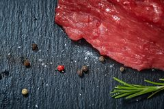 Raw meat beef steaks on black slate board with spices and rosemary, selective focus, shallow depth of field. Raw meat beef steaks on black slate board with Royalty Free Stock Photography
