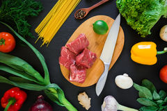 Raw meat on board, knife, pasta and vegetables on dark table. Top view. Flat lay. Raw meat on board, knife, pasta and vegetables on dark table. Top view Stock Photo