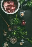 Raw meat with bone in cooking pot on dark kitchen table background with herbs and spices for broth, meat bone stock or soup , top royalty free stock image