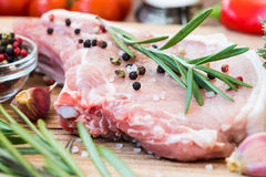 Raw meat on bone with rosemary, thyme, pepper and garlic. Raw meat on the bone with fresh rosemary, thyme, pepper, sea salt and garlic Stock Images