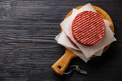Raw meat Burger cutlets. Raw Ground beef meat Burger steak cutlets on black burned wooden background copy space Royalty Free Stock Photo