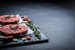 Raw meat burger cutlets with ingredients. Raw cutlet of minced meat with ingredients on a dark cooking background Royalty Free Stock Photography