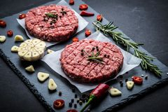 Raw meat burger cutlets with ingredients. Raw cutlet of minced meat with ingredients on a dark cooking background Royalty Free Stock Image