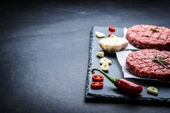 Raw meat burger cutlets with ingredients. Raw cutlet of minced meat with ingredients on a dark cooking background Royalty Free Stock Photo