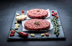 Raw meat burger cutlets with ingredients. Raw cutlet of minced meat with ingredients on a dark cooking background Stock Images