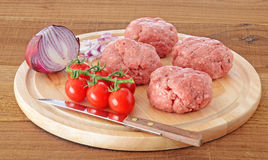 Raw meat burgers on wooden board Stock Photos