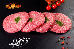 Raw meat. butcher burgers with parsley and tomatoes on black background Royalty Free Stock Photo