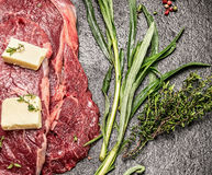 Raw meat with butter, fresh tarragon and thyme on dark stone table, top view Royalty Free Stock Photography
