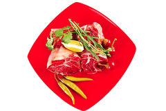 Raw meat chunk on red plate Royalty Free Stock Photos