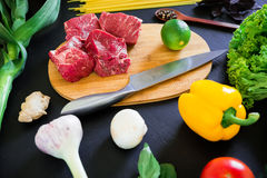 Raw meat on cook board, knife, pasta and fresh vegetables on dark table. Top view. Flat lay. Food background. Raw meat on cook board, knife, pasta and fresh Royalty Free Stock Photography