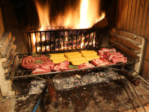 Raw meat  cooking in the fireplace with a warm fire lit Stock Image