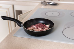 Raw Meat Cooking in Frying Pan on Stove Top Stock Photography